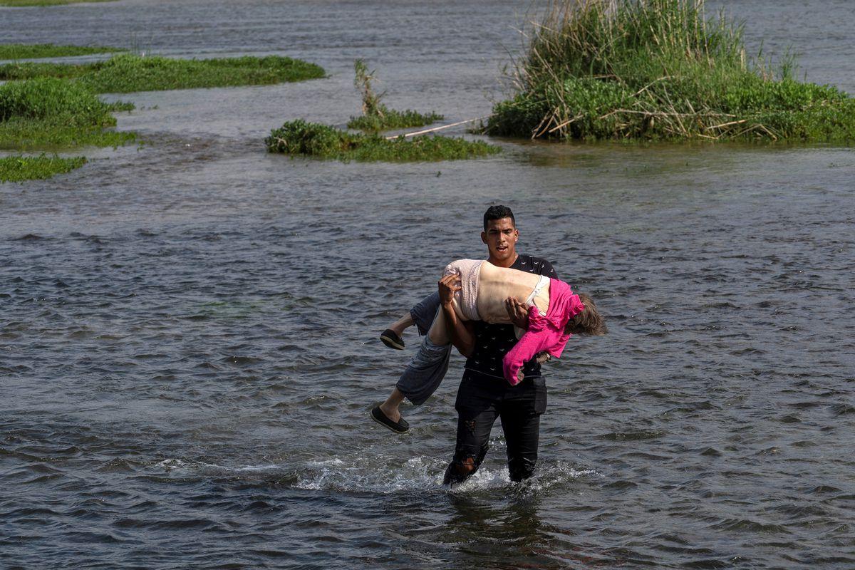 Una anciana de Venezuela cruzando el río Bravo a manos de otro migrante, imagen de dos crisis sin fin